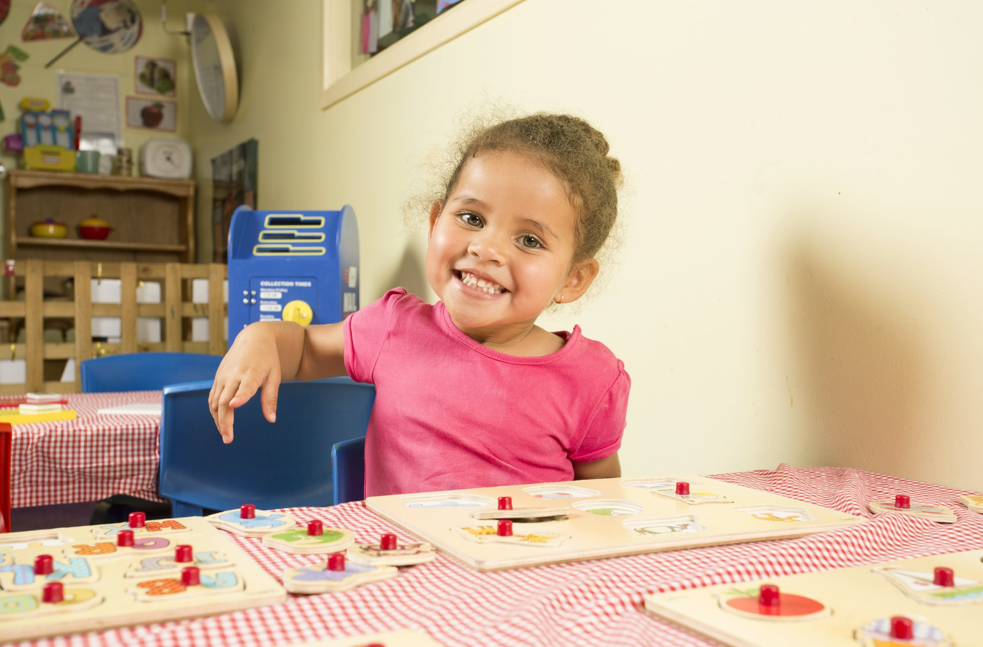 Child smiling in toddler classroom at Village Kids Torquay